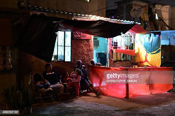 Members of a family watch the show at the BrazilianFrench 'Planeta Ginga' film and music free festival at the Cidade de Deus shantytown in Rio de...