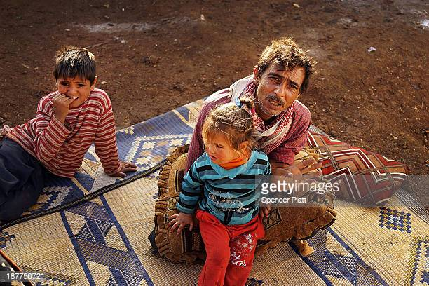 Members of a family who have recently arrived from the besieged Syrian city of Aleppo pause in a makeshift camp in the Bekaa Valley close to the...