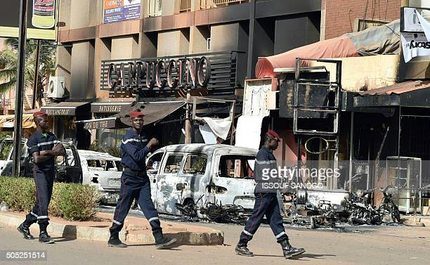 Members of a fire brigade walk past burnt cars outside the Cappuccino restaurant following a jihadist attack in Ouagadougou on January 16 2016 At...