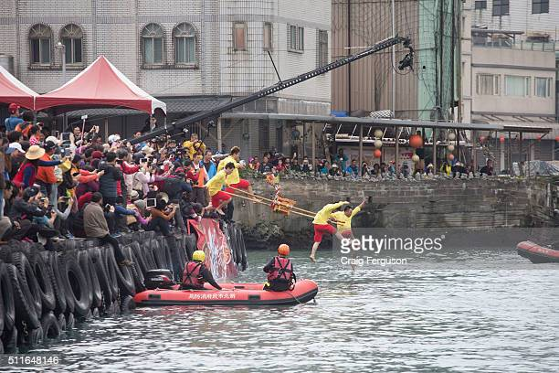 Members of a fishing village's temples jump into the harbour while carrying icons of the gods in an annual harbour cleansing ritual The event acts as...