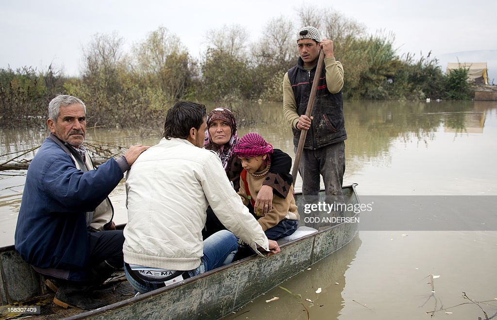 Members of a fleeing Syrian family huddle together aboard a boat that will take them across the Orontes river to Turkey near the northern Syrian town of Darkush on December 13, 2012. The number of Syrian refugees registered in neighbouring countries and North Africa has passed half a million, the UN's refugee body said, adding that many more have not come forward to seek help.