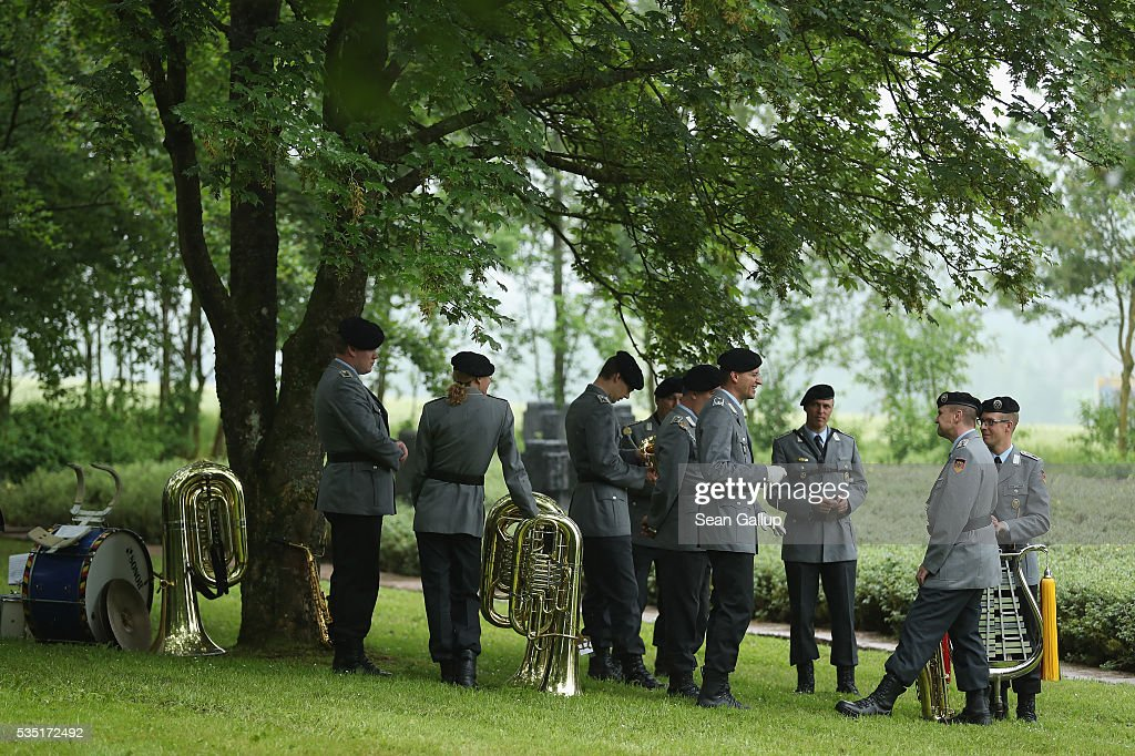 Members of a German Bundeswehr military band take shelter from drizzling rain under a tree before the arrival of French President Francois Hollande and German Chancellor Angela Merkel at the German World War I military cemetery at Consonvoye during ceremonies to commemorate the 100th anniversary of the World War I Battle of Verdun on May 29, 2016 near Verdun, France. The 1916, 10-month battle pitted the French and German armies against one another in a grueling campaign of trench warfare and artillery bombardments that killed a total of approximately 300,000 soldiers. The events today coincide with the 50th anniversary of commemorations held at Verdun by then French President Charles de Gaulle and German Chancellor Konrad Adenauer that paved the way for a new era of peaceful, post-war Franco-German relations.