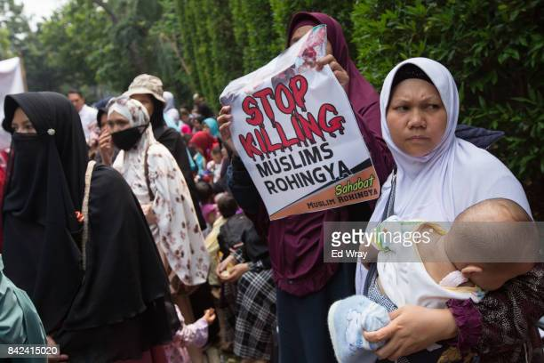 Members of a group calling themselves friends of Muslim Rohingya attend a rally by hundreds of the women's group in front of the Myanmar embassy on...