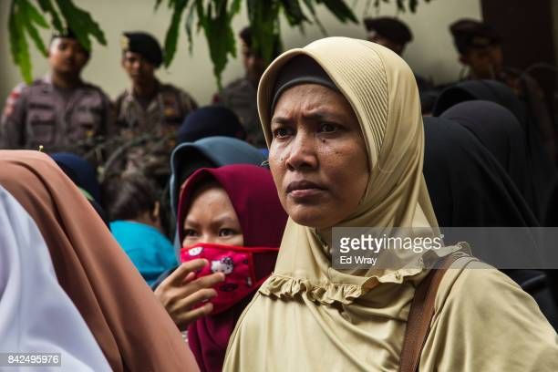 Members of a group calling themselves friends of Muslim Rohingya hold listen to information during a rally by hundreds of the women's group in front...