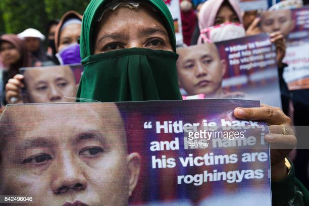 Members of a group calling themselves friends of Muslim Rohingya hold signs and listen to information during a rally by hundreds of the women's group...