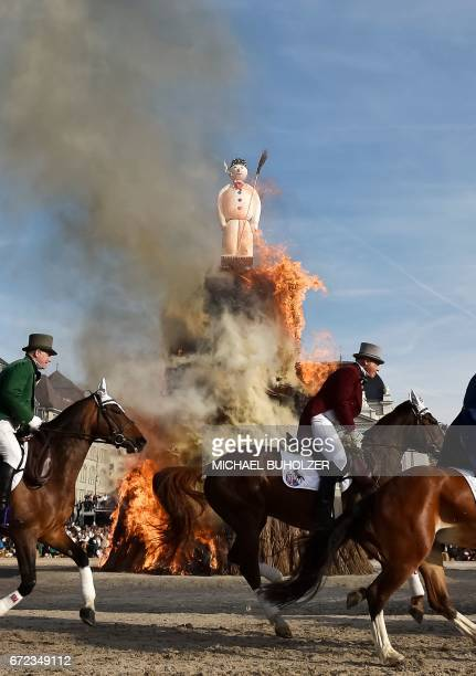 Members of a guild ride around the Boeoegg a giant symbolic snowman made of wadding and and filled with firecrackers burning on top of a bonfire in...
