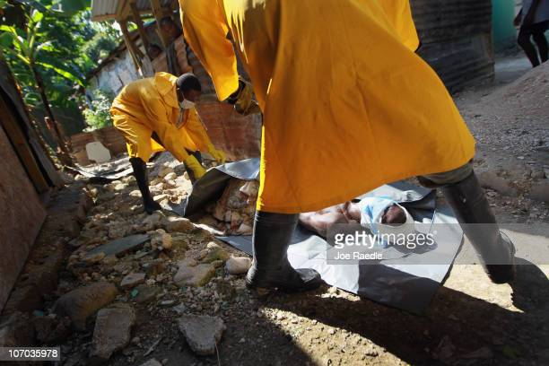 Members of a Haitian Ministry of Health body collection team prepare to zip the body of Nixon Merise into a body bag as they take him from his home...