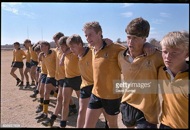 Members of a high school rugby team in South Africa walk off the field with their arms around each other after a game Rugby is a favorite sport among...