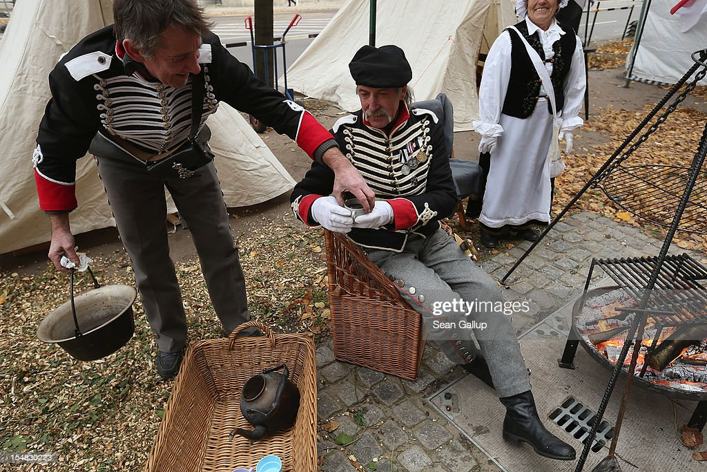 Members of a historical reeneactment club dressed as a Prussian Husar regiment that served under Napoleon warm themselves with mulled wine during celebrations marking the 775th anniversary of Berlin on October 27, 2012 in Berlin, Germany. Celebrations are continuing over the weekend and will culminate in a fire presentation by the French fire performers Carabosse on Sunday. The settlement of Coelln, which stood opposite Berlin on the Spree river, is first referred to in a document from 1237, and by the beginning of the 14th century Coelln and Berlin joined together to become the region's most important trading center.