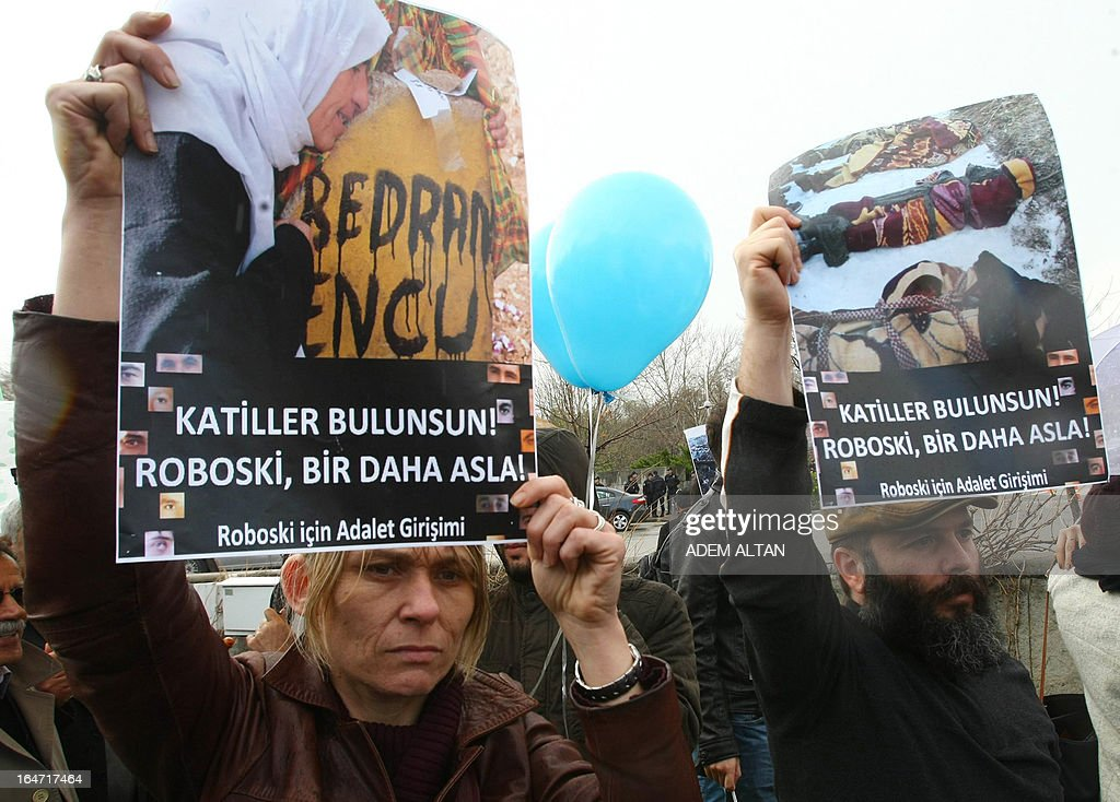 Members of a human rights groups march on March 27, 2013 to the Turkish Parliament in Ankara with placards, reading: 'Perpetrators should be found. Uludere (Roboski) never again!', during a protest about the December 2011 killing of 34 Turkish Kurdish civilians at the Turkish-Iraqui in a botched raid by Turkish military jets that mistook the group for Kurdish rebels based in Iraq. A recent parliamentary report on the massacre concluded that the Turkish military's air strike was not deliberate. AFP PHOTO/ADEM ALTAN