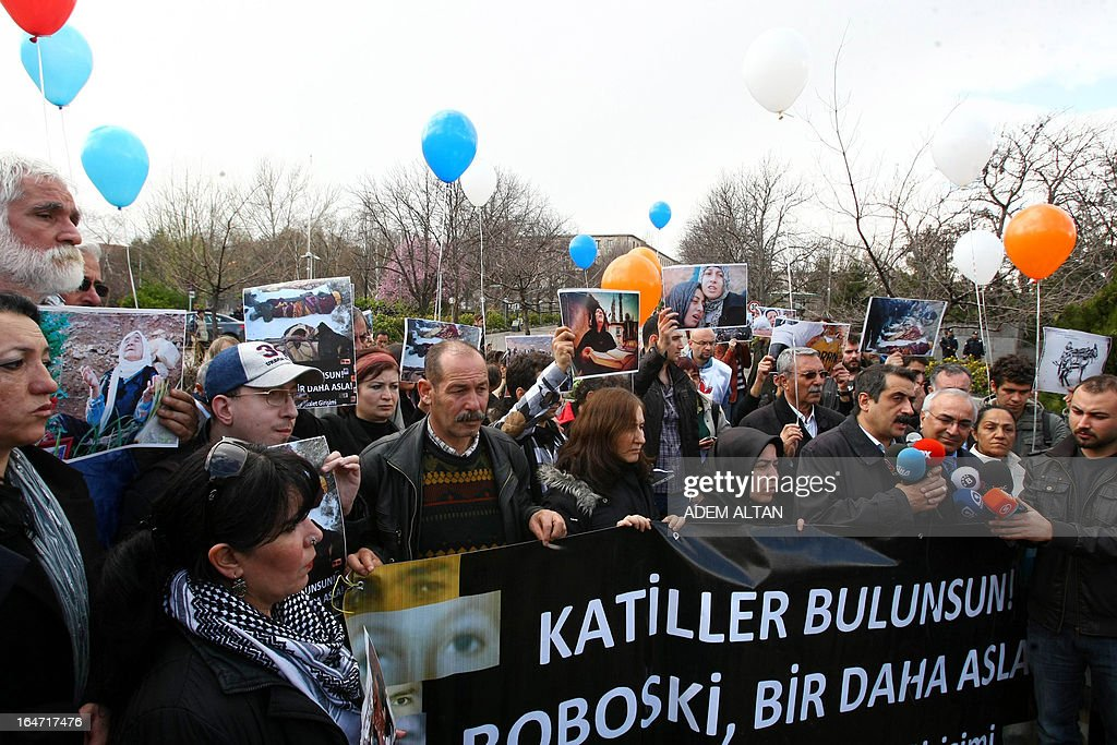Members of a human rights groups march on March 27, 2013 to the Turkish Parliament in Ankara with a banner, reading: 'Perpetrators should be found. Uludere (Roboski) never again!', during a protest about the December 2011 killing of 34 Turkish Kurdish civilians at the Turkish-Iraqui in a botched raid by Turkish military jets that mistook the group for Kurdish rebels based in Iraq. A recent parliamentary report on the massacre concluded that the Turkish military's air strike was not deliberate. AFP PHOTO/ADEM ALTAN