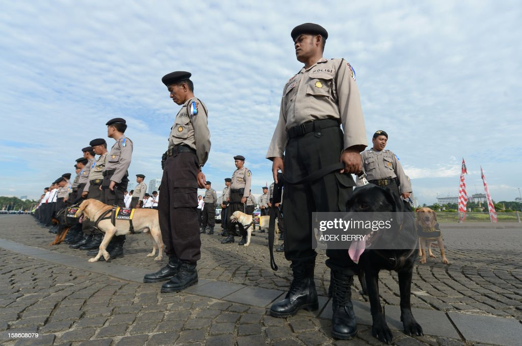 Members of a K-9 squad stand with police as they attend a security roll call ahead of the Christmas and New Year Eve festivities in Jakarta on December 21, 2012. Indonesia's government will beef up its security by deploying around 82,000 policemen across the country to operate from December 23 to January 1. Indonesian was rocked by a series of coordinated bomb blasts at several churches and police stations nationwide on Christmas Eve in 2000. AFP PHOTO / ADEK BERRY