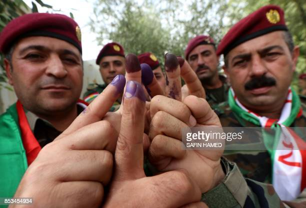 Members of a Kurdish Peshmerga battalion show their inkstained fingers after voting in the Kurdish independence referendum in Arbil the capital of...