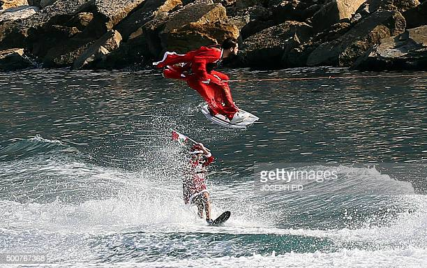 Members of a Lebanese water sports club dressed in Santa Claus uniforms perform a water skiing stunt off of the coastal town of Jounieh north of the...