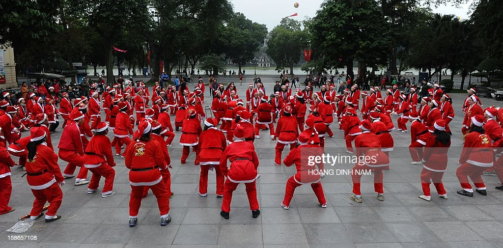 Members of a local Smiling Yoga club wearing Santa Claus costumes perform at a public park in Hanoi on December 23, 2012. Churches, shops, restaurants and shopping mails are decorated in the Southeast Asian nation with some six million catholics preparing to celebrate Christmas. AFP PHOTO / HOANG DINH Nam