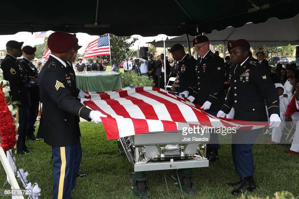 Members of a military honor guard prepare to fold the flag above the casket of US Army Sgt La David Johnson during his burial service at the Memorial...