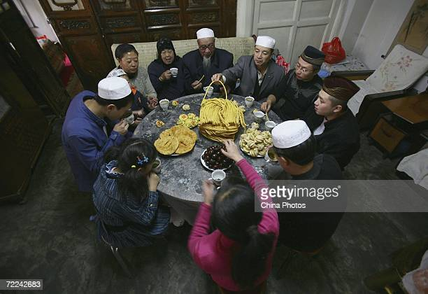 Members of a Muslim family have a feast to mark the EidalFitr Festival at their home on October 23 2006 in Xining of Qinghai Province China EidalFitr...