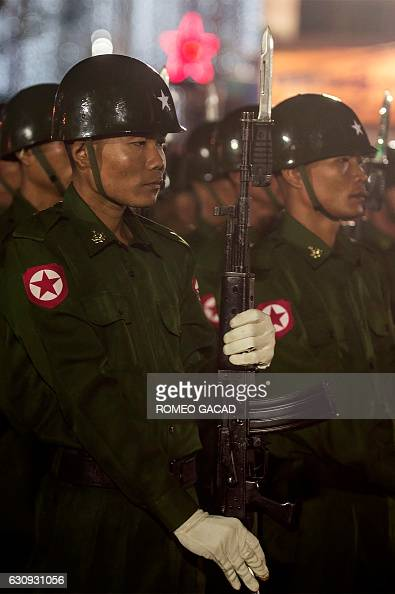 Members of a Myanmar military honour guard raise their bayonetmounted rifles in a salute during a dawn flagraising ceremony at Yangon's central...