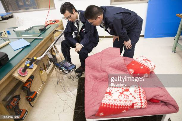 Members of a Nitori Holdings Co quality control team conduct heat test on a 'kotatsu' a kind of Japanese table during a product test in Tokyo Japan...