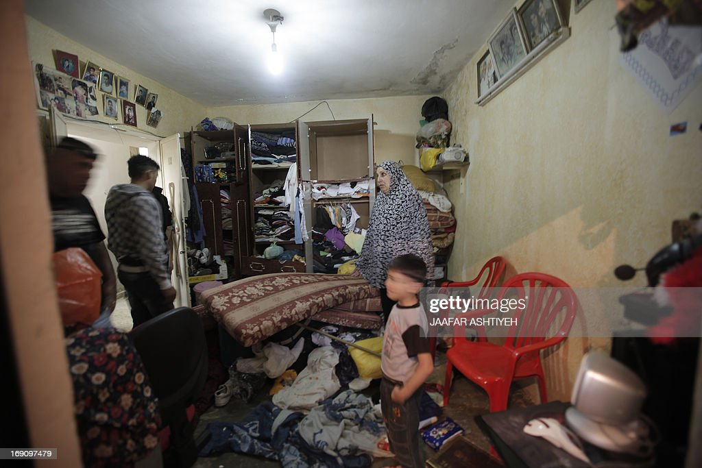 Members of a Palestinian family inspect an overturned room following an Israeli army house search during an operation to arrest wanted Palestinians in the occupied West Bank village of Kfar Qaleel close to the West Bank city of Nablus on May 20, 2013. PHOTO