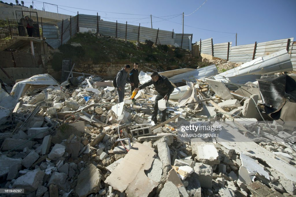 Members of a Palestinian family look for salvageable items after Israeli bulldozers demolished their family house in the Arab East Jerusalem neighborhood of Beit Hanina on February 18, 2013. Palestinian homes built without a construction permit are often demolished by order of the Jerusalem municipality.