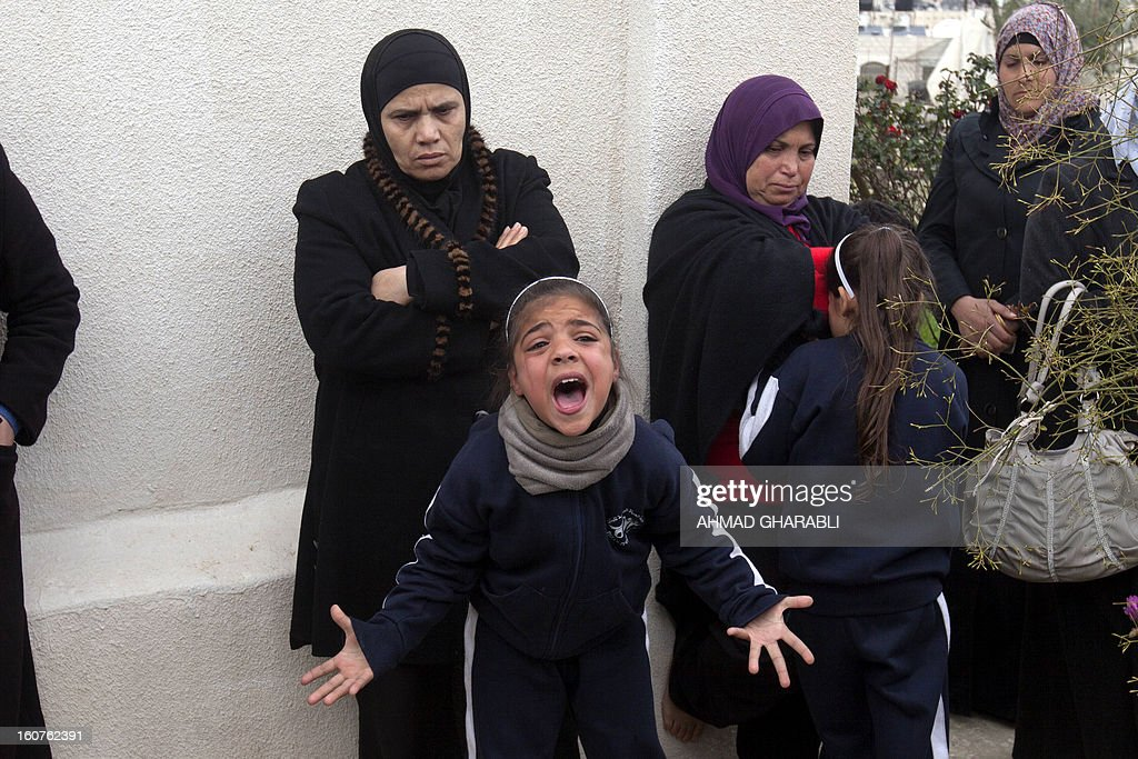 Members of a Palestinian family react after Israeli bulldozers demolished their family house in the Arab east Jerusalem neighborhood of Beit Hanina on February 5, 2013. Palestinian homes built without a construction permit are often demolished by order of the Jerusalem municipality.