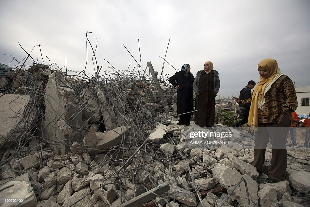 Members of a Palestinian family react after Israeli bulldozers demolished their family house in the Arab east Jerusalem neighborhood of Beit Hanina on February 5, 2013. Palestinian homes built without a construction permit are often demolished by order of the Jerusalem municipality. AFP PHOTO/AHMAD GHARABLI