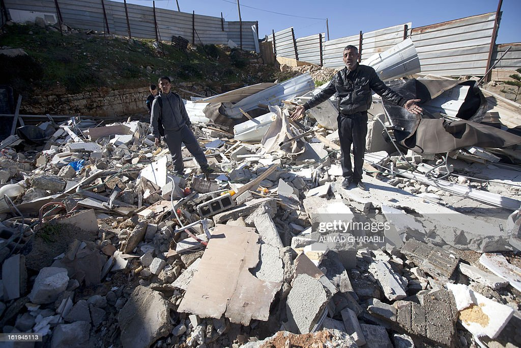 Members of a Palestinian family react after Israeli bulldozers demolished their family house in the Arab East Jerusalem neighborhood of Beit Hanina on February 18, 2013. Palestinian homes built without a construction permit are often demolished by order of the Jerusalem municipality. AFP PHOTO/AHMAD GHARABLI
