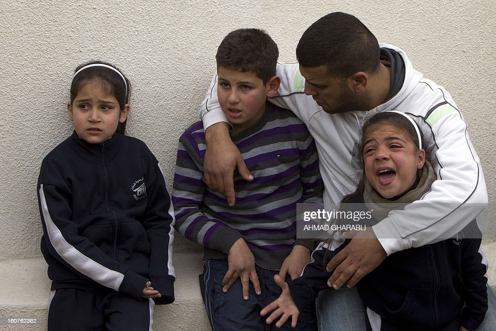 Members of a Palestinian family react as they watch Israeli bulldozers demolishing their family house in the Arab east Jerusalem neighborhood of Beit Hanina on February 5, 2013. Palestinian homes built without a construction permit are often demolished by order of the Jerusalem municipality. AFP PHOTO/AHMAD GHARABLI