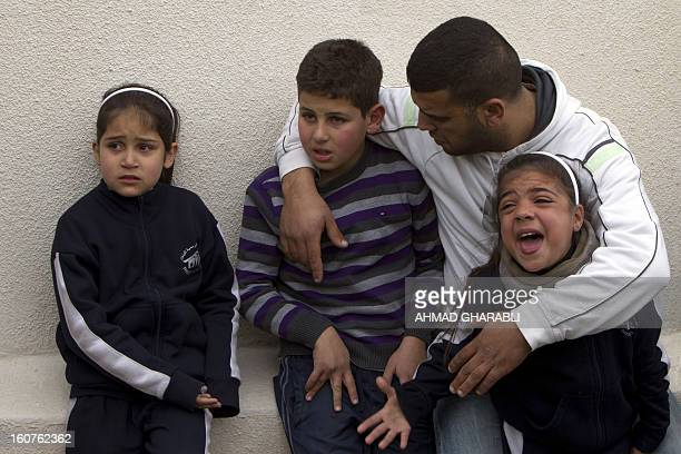Members of a Palestinian family react as they watch Israeli bulldozers demolishing their family house in the Arab east Jerusalem neighborhood of Beit...