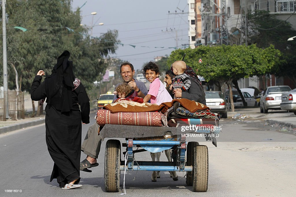 Members of a Palestinian family ride on a four-wheeled cart drawn by a donkey in Gaza City as displaced Gazans returned to their homes after an eight-day conflict on November 22, 2012. A ceasefire took hold in and around Gaza after a week of cross-border violence between Israel and Palestinian militants that killed at least 160 people.