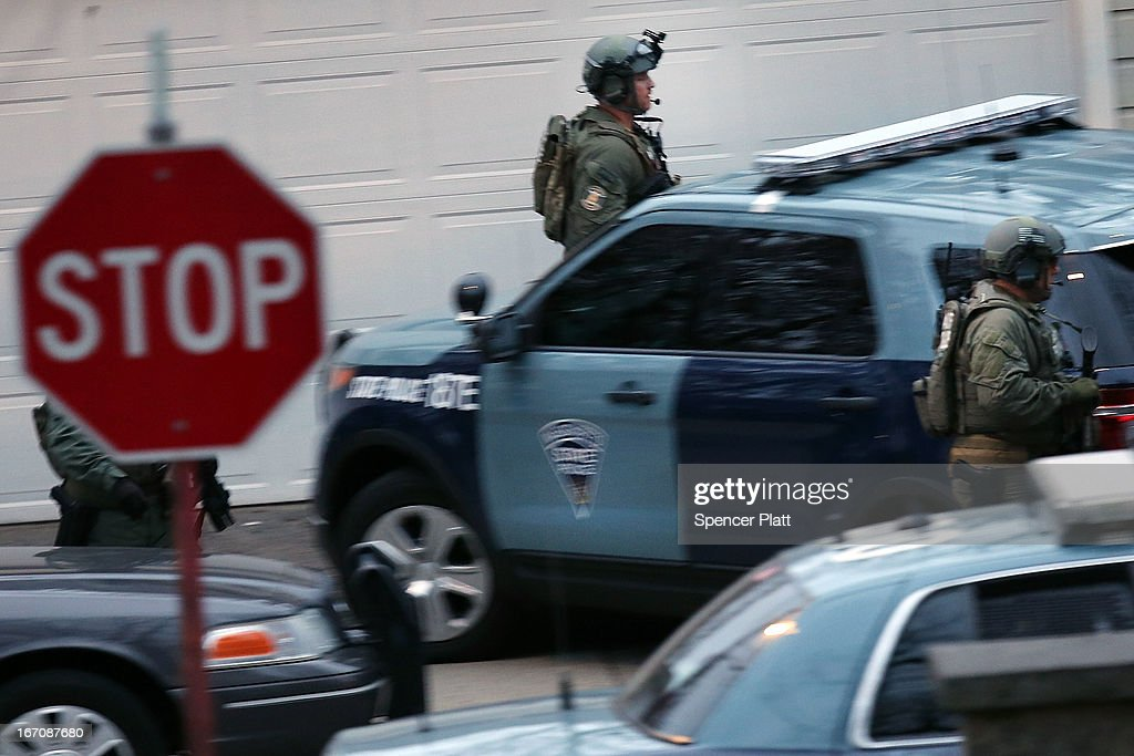 Members of a police SWAT team run to the scene where it was believed 19yearold bombing suspect Dzhokhar A Tsarnaev is in hiding on April 19 2013 in...