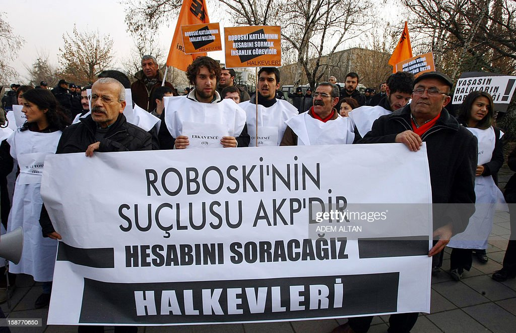 Members of a pro-Kurdish party stage a protest against the Turkish government in Ankara on December 28, 2012 on the first anniversary of a Turkish military air strike aimed at Kurdish rebels that killed 34 civilians at the Turkey-Iraq border. The banner reads 'AKP is responsable for the Roboski (Uludere) massacre. It will pay for it.'