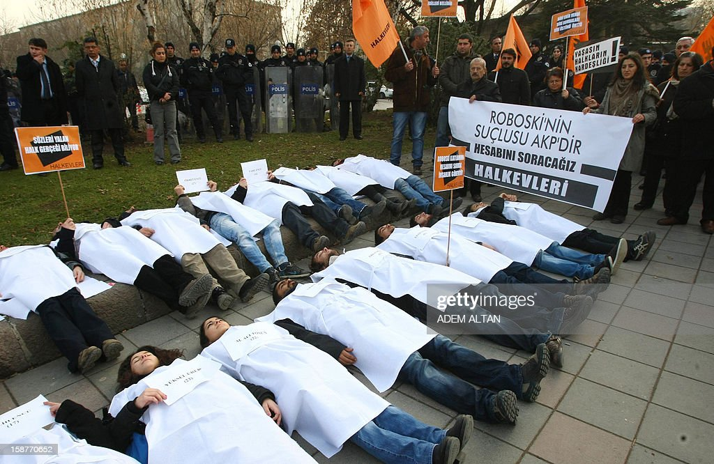 Members of a pro-Kurdish party stage a protest against the Turkish government in Ankara on December 28, 2012 on the first anniversary of a Turkish military air strike aimed at Kurdish rebels that killed 34 civilians at the Turkey-Iraq border. The banner reads 'AKP is responsable for the Roboski (Uludere) massacre. It will pay for it.' AFP PHOTO/ADEM ALTAN