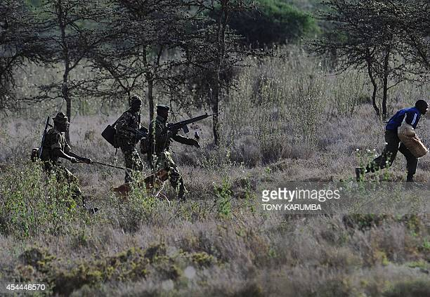 Members of a ranger elite team run after a 'poacher' during a drill on August 6 2014 at the Ol Jogi rhino sanctuary in the Laikipia county...