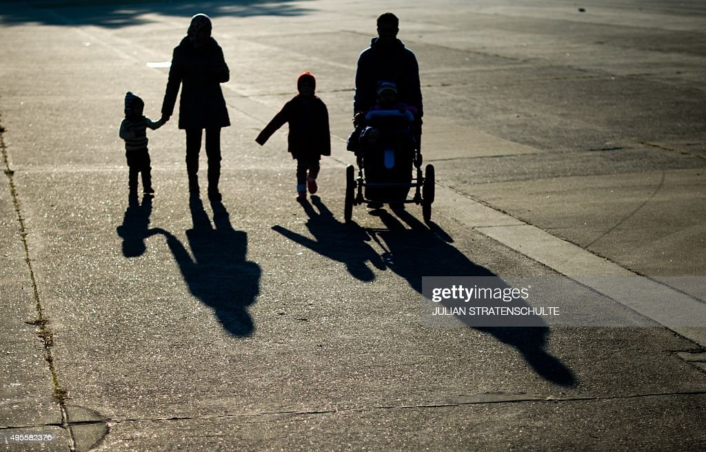 Members of a refugee family from Syria cast long shadows as they walk over the grounds of former military barracks serving now as shelter for asylum...