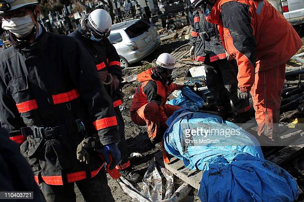 Members of a rescue team cover a body found on the side of the road on March 18 2011 in Ishinomaki Japan Residents are starting to return to their...