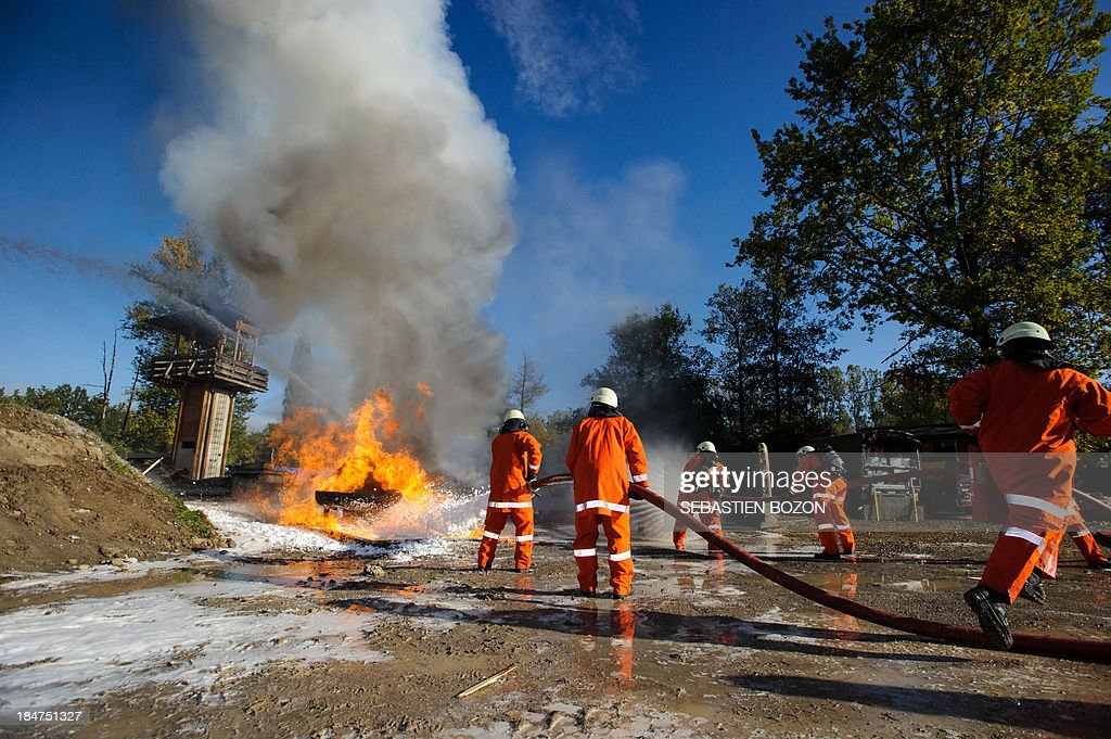 Members of a rescue troop extinguish a fire during a practice session at a Swiss military base on October 16, 2013 in Bremgarten. AFP PHOTO / SEBASTIEN BOZON
