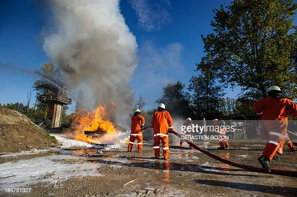 Members of a rescue troop extinguish a fire during a practice session at a Swiss military base on October 16 2013 in Bremgarten AFP PHOTO / SEBASTIEN...