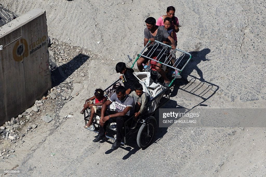 Members of a Roma family ride a tricycle packed with sacks to collect plastic and aluminum waste from the rubbish bins for sale to the recycling industry in Tirana on June 11, 2014. Unemployment rose to 18.3% in the first quarter of 2014 in Albania, despite the efforts of the new government to create more jobs, including for the Roma community. AFP PHOTO / GENT SHKULLAKU