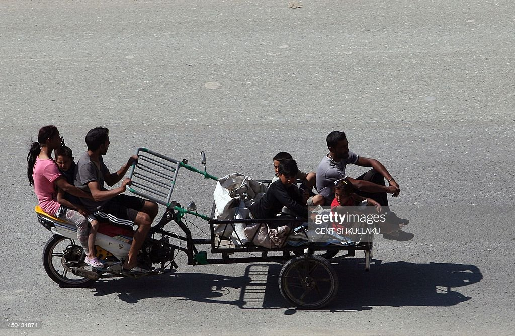 Members of a Roma family ride a tricycle packed with sacks to collect plastic and aluminum waste from the rubbish bins for sale to the recycling industry in Tirana on June 11, 2014. Unemployment rose to 18.3% in the first quarter of 2014 in Albania, despite the efforts of the new government to create more jobs, including for the Roma community.