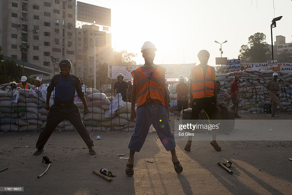 Members of a security team and supporters of deposed Egyptian President Mohammed Morsi take part in morning exercises at a sit-in demonstration near the Rabaa al-Adweya Mosque in the Nasr City district on August 12, 2013 in Cairo, Egypt. Egyptian security forces threatened to begin a siege of pro-Morsi protest camps in Cairo overnight on August 11, however Egypt's Interior Ministry appeared to have put off plans to crack down on protesters early on Monday. Morsi supporters have continued to protest at sites across Cairo over one month after the Egyptian military deposed Egypt's first democratically elected President, Mohammed Morsi, on July 3. (Photo by Ed Giles/Getty Images).