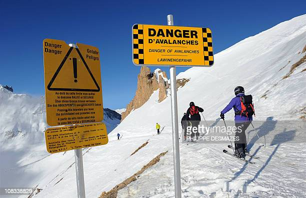 EMONET Members of a ski patrol set a banner warning skiers of the danger of avalanche on January 19 2011 in Tignes eastern France AFP PHOTO/PHILIPPE...