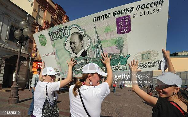 Members of a social network group 'I Really Like Putin' carry a one thousand ruble banknote in Moscow on August 18 during their action in support of...