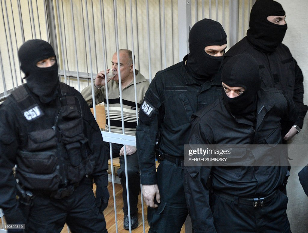 Members of a special police unit stand guard on January 29, 2013 at a Kiev district court as the former chief of the external surveillance department of the Ukrainian Interior Ministry, Oleksiy Pukach (2nd L), drinks water after the verdict reading of his trial for the 2000 murder of opposition journalist Georgy Gongadze. Pukach was sentenced to a life term over the journalist's murder.