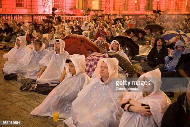 Members of a stoic audience try to ignore the rain as they watch the Coen brother's cult film 'The Big Lebowski' on a giant screen within the...