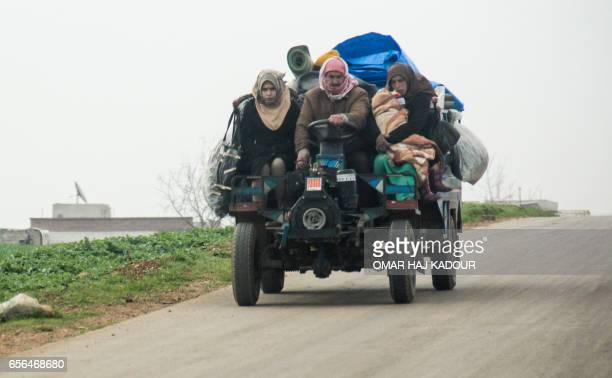 TOPSHOT Members of a Syrian family displaced due to airstrikes travel with their belongings in a farming vehicle along a road near the town of...