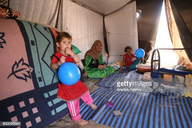 Members of a Syrian family pose inside their tent during Muslim's holy month of Ramadan in Idlib Syria on June 23 2017 Ahead of Eid al Fitr Syrian...