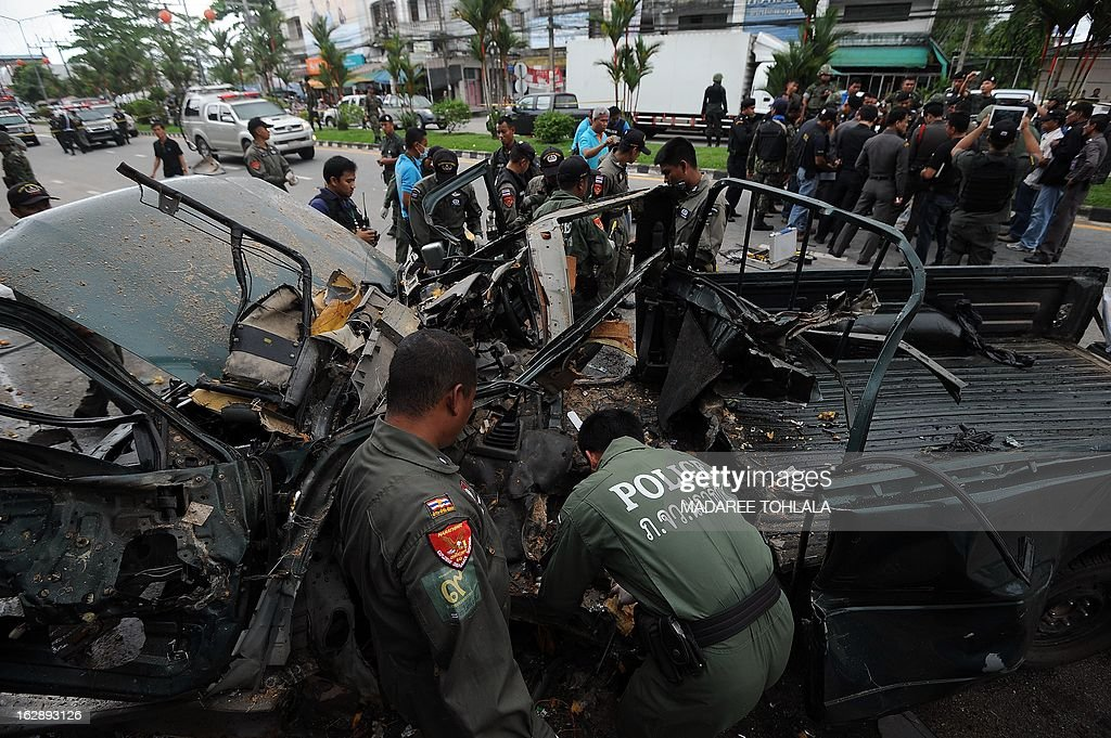 Members of a Thai bomb squad inspect the site of a car bomb blast triggered by suspected separatist militants in front of a police station in Thailand's restive southern province of Narathiwat on March 1, 2013. At least six people were injured when blasts rattled the restive Thai south on March 1, police said, as unrest continued barely a day after Thailand signed a peace talk deal with one of several rebel groups. AFP PHOTO/Madaree TOHLALA