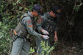 Members of a Thai bomb squad unit inspect a road side area after a bomb blast triggered by suspected separatist militants in Thailand's restive...